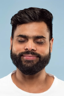 Bouchent le portrait de jeune homme hindou avec barbe en chemise blanche isolé sur fond bleu. émotions humaines, expression faciale, concept publicitaire. espace négatif. rêver les yeux fermés.