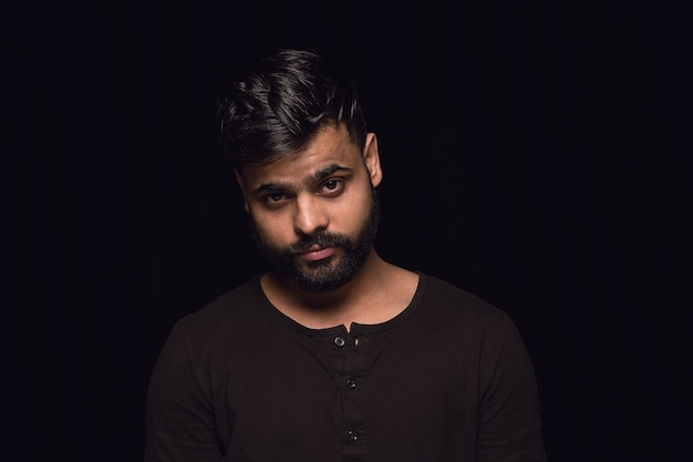 Bouchent le portrait de jeune homme hindou isolé sur le mur noir du studio