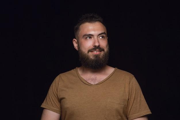 Bouchent le portrait de jeune homme isolé sur fond noir de studio. photoshot des émotions réelles du modèle masculin. rêver et souriant, plein d'espoir et heureux. expression faciale, concept d'émotions humaines.