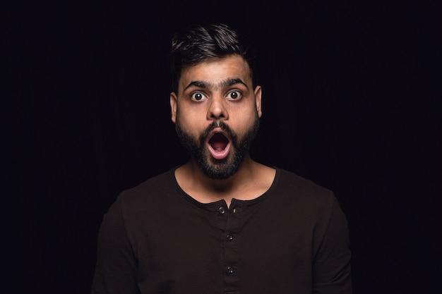 Bouchent le portrait de jeune homme isolé sur fond noir de studio. photoshot des émotions réelles du modèle masculin. vous vous demandez, passionnant et étonné. expression faciale, concept d'émotions humaines.