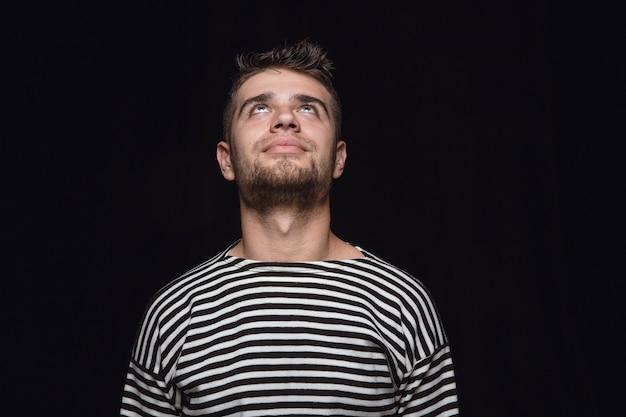 Bouchent le portrait de jeune homme isolé sur fond noir de studio. photoshot des vraies émotions du modèle masculin. rêver et souriant, plein d'espoir et heureux. expression faciale, concept d'émotions humaines.