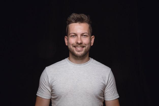 Bouchent le portrait de jeune homme isolé sur fond noir de studio. sourire, se sentir heureux.