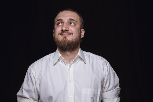 Bouchent le portrait de jeune homme isolé sur fond noir de studio.