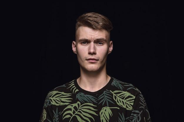Bouchent le portrait de jeune homme isolé sur fond noir