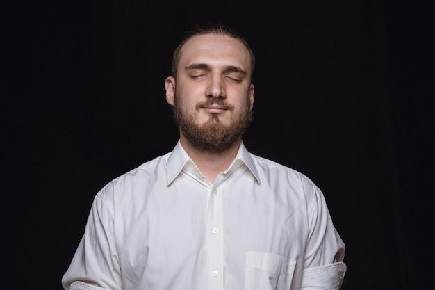 Bouchent le portrait de jeune homme isolé sur le mur noir du studio