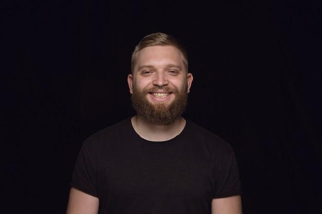 Bouchent le portrait d'un jeune homme isolé sur un mur noir. photoshot des émotions réelles du modèle masculin. sourire, se sentir heureux. expression faciale, concept d'émotions humaines pures et claires.
