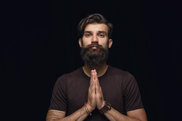 Bouchent le portrait de jeune homme isolé sur mur noir