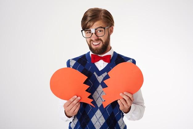 Bouchent le portrait de jeune homme tenant une forme de coeur brisé