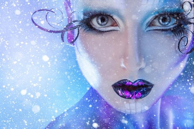 Bouchent le portrait de jeune mannequin adulte regardant la caméra avec maquillage créatif et neige
