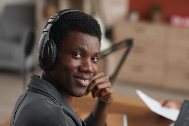 Bouchent le portrait de jeune musicien afro-américain portant des écouteurs et souriant à la caméra tout en composant de la musique au studio d'enregistrement à domicile, espace copie