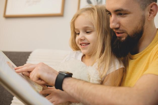 Bouchent le portrait d'un jeune père caucasien barbu, lisant un livre avec sa petite jolie fille blonde sur le canapé le matin à la maison.