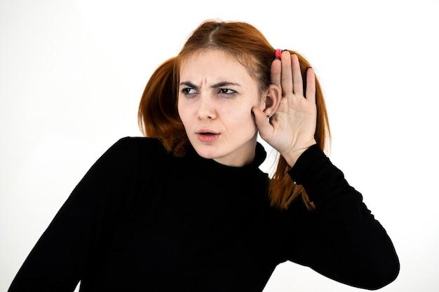 Bouchent le portrait d'une jolie adolescente rousse tenant une main à son oreille écoutant un secret.