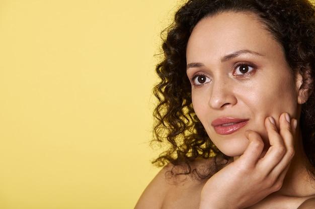 Bouchent le portrait d'une jolie femme aux cheveux bouclés à la recherche de suite isolé sur jaune avec copie espace