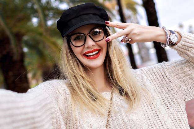 Bouchent le portrait de jolie femme blonde portant une tenue décontractée à la mode, rouge à lèvres et lunettes claires, manucure et bijoux, émotions surprises, posant dans la rue avec des palmiers, voyager seul.