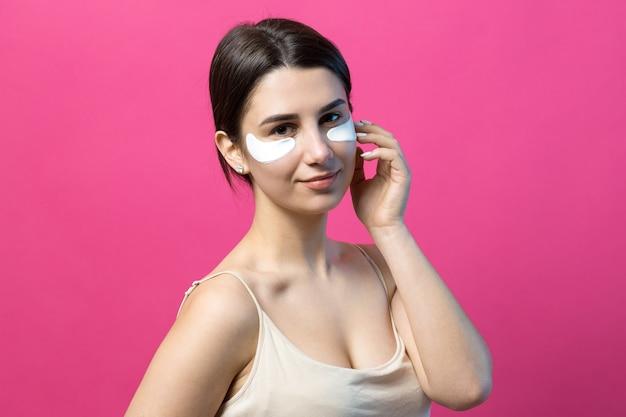 Bouchent le portrait d'une jolie fille attirante avec des épaules nues à l'aide de patchs sous les yeux