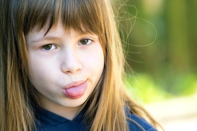 Bouchent le portrait d'une jolie fille montrant la langue et regardant la caméra.