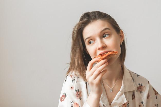 Bouchent le portrait d'une jolie fille mord un morceau de pizza et regarde de côté sur un gris