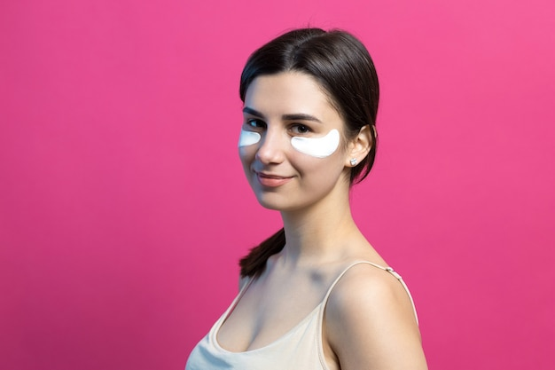 Bouchent le portrait d'une jolie fille séduisante aux épaules nues à l'aide de patchs sous les yeux. debout sur fond rose.