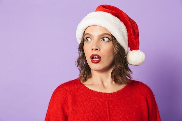 Bouchent le portrait d'une jolie jeune femme portant un chapeau de noël rouge à l'écart, isolé sur mur violet