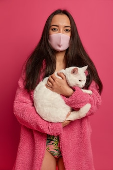 Bouchent le portrait de la jolie jeune femme portant un masque protecteur isolé