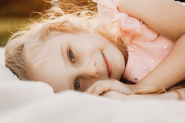 Bouchent le portrait d'une jolie jeune fille regardant la caméra en souriant. mignon petit enfant appuyé sur le sol contre le coucher du soleil en jouant.
