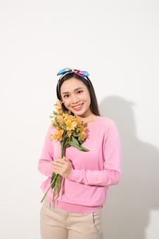Bouchent le portrait d'une jolie jolie femme adorable excitée adorable tenant des fleurs isolée