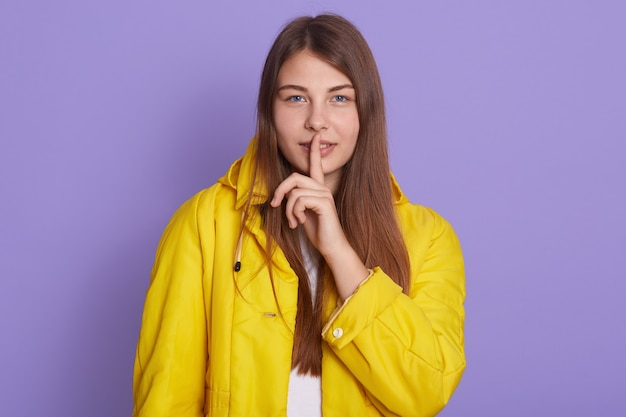 Bouchent le portrait de jolie jolie femme séduisante tenant l'index près des lèvres isolées sur fond lilas, a une expression faciale confiante, vêtue d'une veste jaune vif, garde des informations secrètes.