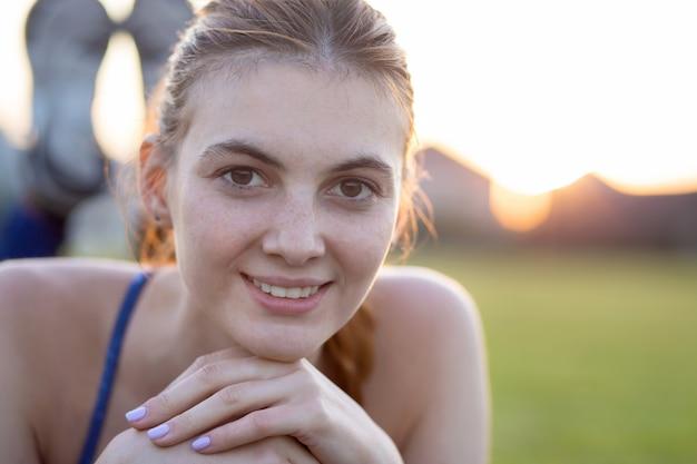Bouchent le portrait de joyeuse jeune fille souriante avec des taches de rousseur sur son visage à l'extérieur en journée d'été ensoleillée. concept d'expressions et d'émotions humaines.