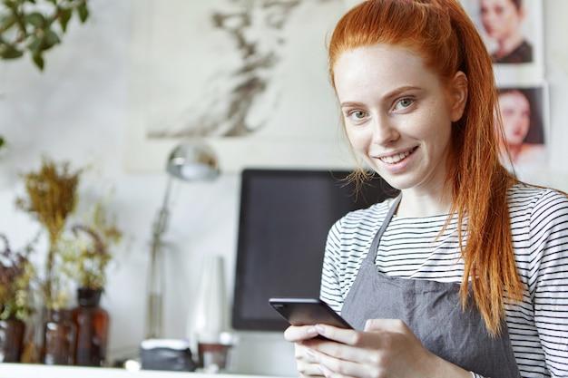 Bouchent le portrait de joyeuse jolie jeune femme d'occupation créative portant ses longs cheveux roux en queue de cheval en tapant un message texte à l'aide de son téléphone mobile
