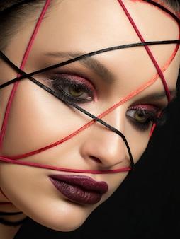 Bouchent le portrait de mode de la belle jeune femme avec un maquillage tendance moderne. yeux et lèvres charbonneux rouge foncé.