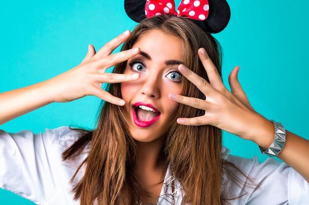 Bouchent le portrait de la mode élégante fille, peau parfaite, maquillage éclatant, poils brune, beauté pure, ferme les yeux et souriant, dents blanches et lèvres pleines, fond de studio bleu.