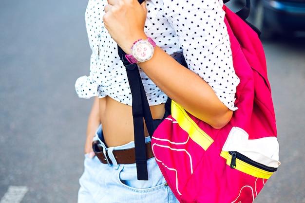 Bouchent le portrait de mode de jeune femme élégante, voyageant seule avec sac à dos lumineux, vêtements à la mode décontractés. fille de hipster marchant dans la rue, détails de mode