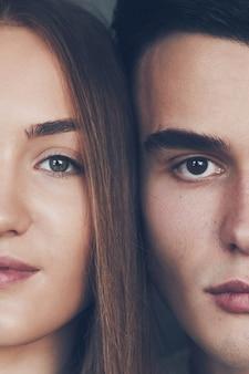 Bouchent le portrait de la moitié des visages homme et femme regardant la caméra.