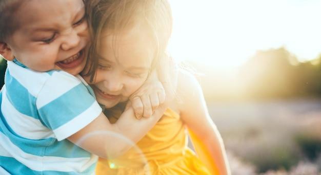 Bouchent le portrait d'un petit garçon caucasien embrassant sa sœur tout en jouant ensemble à l'extérieur