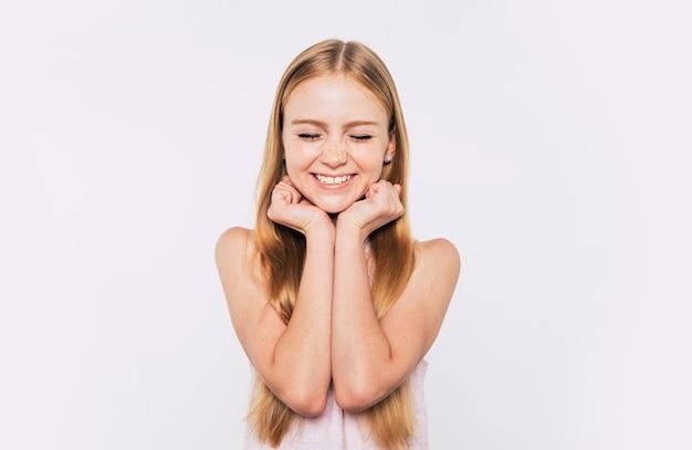 Bouchent le portrait d'une petite fille blonde attirante et mignonne aux cheveux longs pendant qu'elle pose isolée sur fond blanc et souriante