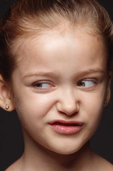Bouchent le portrait de petite fille caucasienne et émotionnelle. séance photo très détaillée d'un modèle féminin avec une peau bien entretenue et une expression faciale brillante. concept d'émotions humaines. répugnant.