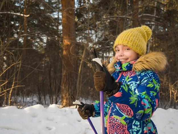 Bouchent le portrait d'une petite fille pendant la marche nordique dans la forêt d'hiver.