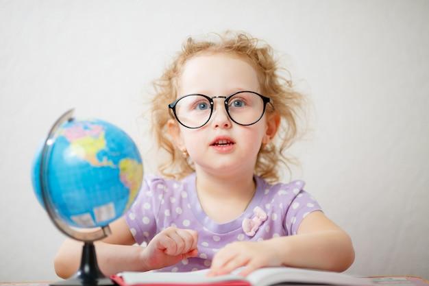 Bouchent le portrait photo de petite fille drôle avec des lunettes. elle feuillette le livre sur la table est un globe