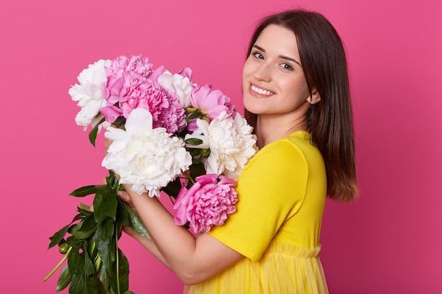Bouchent le portrait de profil de jolie femme élégante en t-shirt décontracté jaune isolé sur studio rose, tenant le bouquet de fleurs de pivoine, femme avec une expression faciale heureuse. concept d'amour.