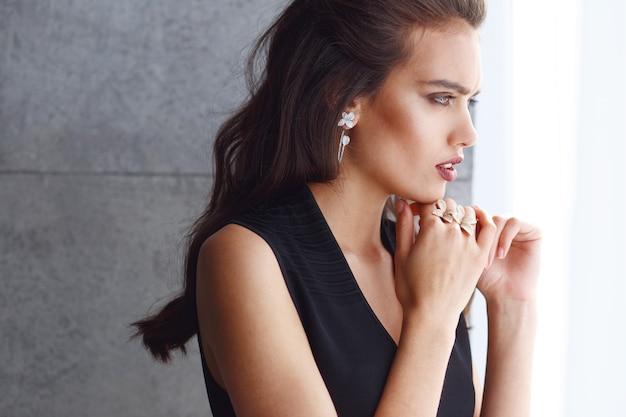 Bouchent le portrait de profil d'une jolie jeune femme brune, regardant par la fenêtre