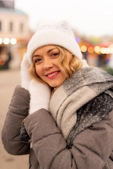 Bouchent le portrait de rue de sourire belle jeune femme sur la foire de noël festive. dame portant des vêtements tricotés d'hiver classiques et élégants.
