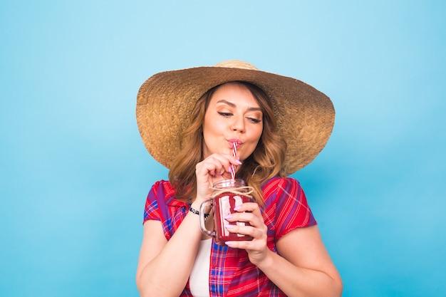 Bouchent le portrait en studio d'une femme sexy portant une tenue lumineuse tenant et buvant un délicieux milk-shake de smoothie vert. sur fond bleu et copiez l'espace.
