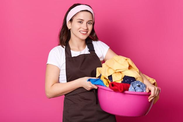 Bouchent portrait en studio de joyeuse femme mignonne souriante ayant bassin rose avec du linge dans les deux mains, semble positive et heureuse. belle femme au foyer douce se tient isolée sur le mur rose.