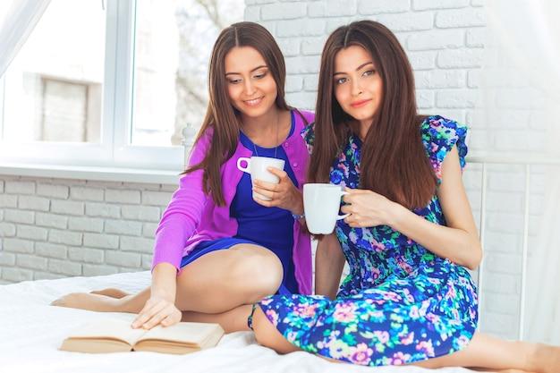 Bouchent le portrait de style de vie intérieur de deux filles assez gaies tient une tasse de café.