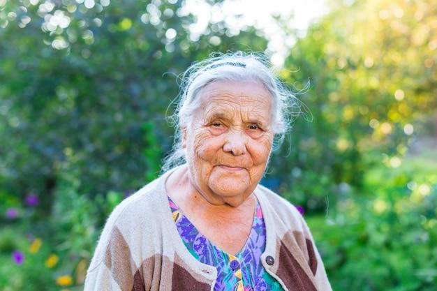 Bouchent le portrait d'une très vieille femme ridée de quatre-vingt ou quatre-vingt-dix ans, regardant la caméra, restant dans son jardin. concept de vieillesse et de style de vie. processus de vieillissement.