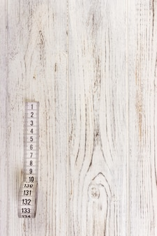 Bouchent le ruban à mesurer sur mesure sur fond de table en bois. ruban à mesurer blanc à faible profondeur de champ.