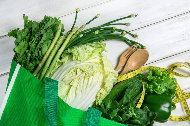 Bouchent un sac d'épicerie vert de mélange de légumes verts biologiques sur blanc