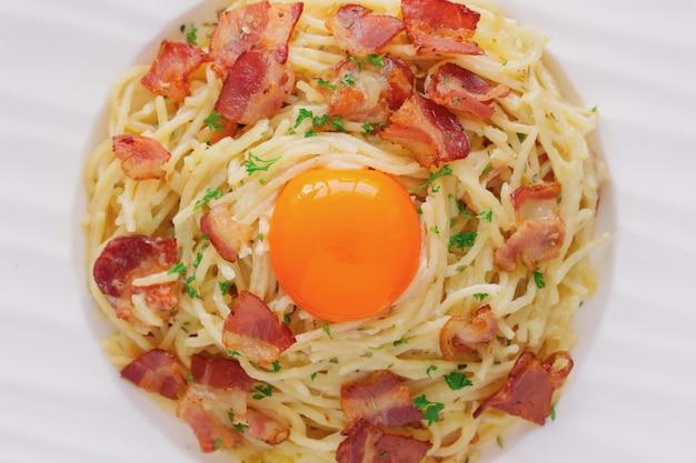 Bouchent les spaghettis carbonara avec du bacon, du fromage, du jaune et du persil.