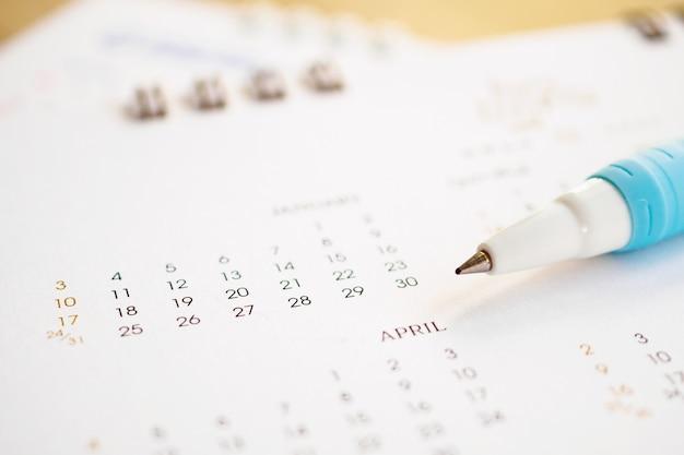 Bouchent le stylo sur la page de calendrier pour marquer le concept de planification de date