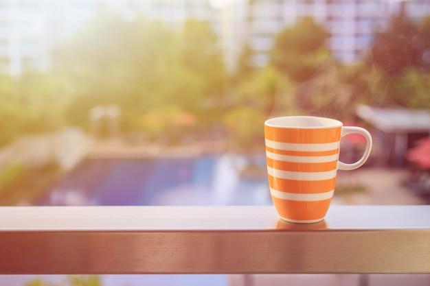 Bouchent la tasse de café orange sur le balcon de l'hôtel et vue floue du bâtiment